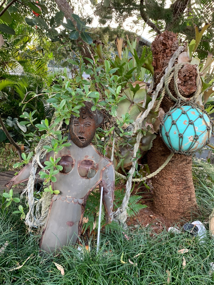 Native garden decoration: tin female form and old bouys and ropes washed up from the beach
